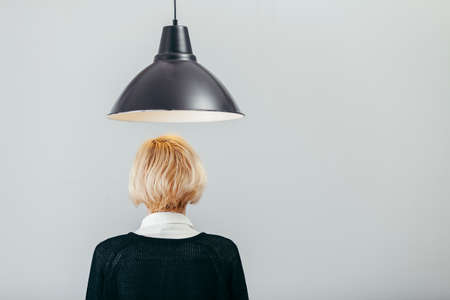 back of head: creative thinking concept with a lamp and back head of blond lady