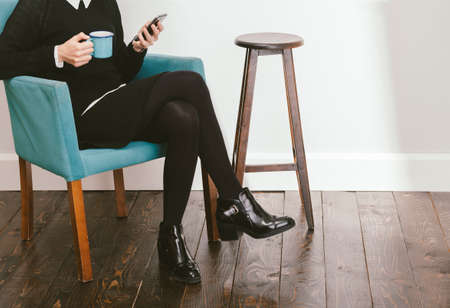 blogger: blogger girl checkig her smartphone while drinking a coffee