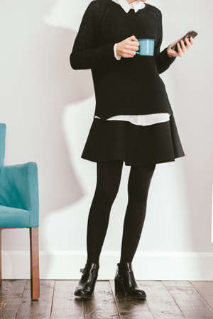 stockings heels: blogger girl checkig her smartphone while drinking a coffee