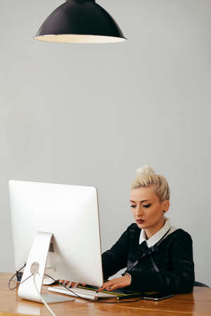 homely: young blond woman working at homely office