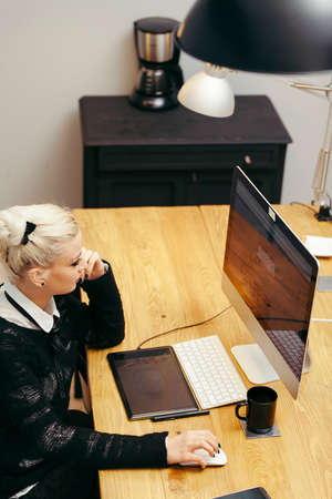 working woman: young blond woman working at homely office