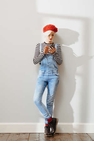 floor standing: young fashionable lady in an empty room with wooden floor and using her smartphone Stock Photo