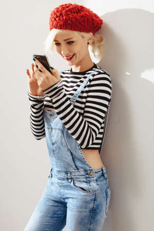 young lady: young fashionable lady leaning on a wall and using her smartphone