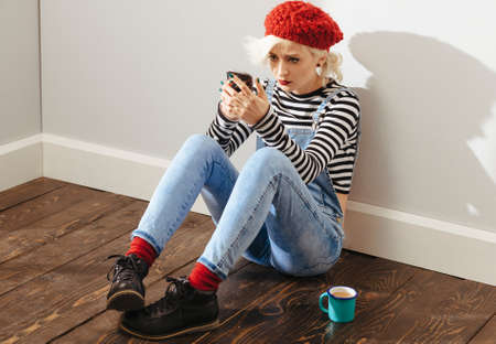 young lady: young fashionable lady sitting in an empty room with wooden floor and using her smartphone Stock Photo