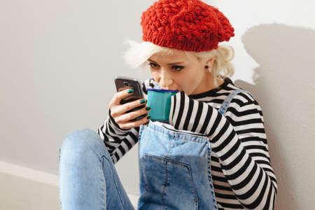 young fashionable lady sitting in an empty room and using her smartphone photo
