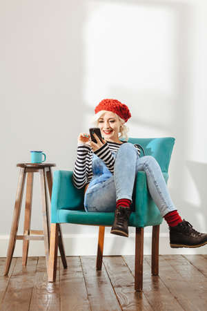 young fashionable lady sitting in an empty room with wooden floor and using her smartphone photo