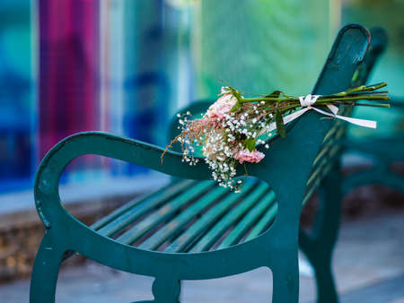 A bouquet of flowers lying on a park bench Stock Photo