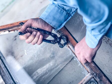 Worker man repairs an old wooden window frame with a pair of nail puller pliers. Close-up of DIY