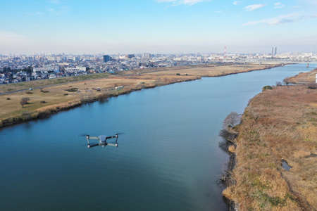 A small drone flying over the Edo River Stock Photo
