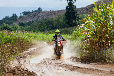 piloting: CHIANG MAI, THAILAND - OCT 2: Unknown Motorcycle driver piloting his Motocross on the tracks, Oct 2, 2016 in Chiang Mai, Thailand.