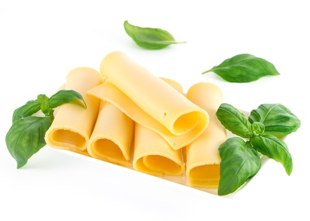Cheese and basil leaves isolated on white background photo