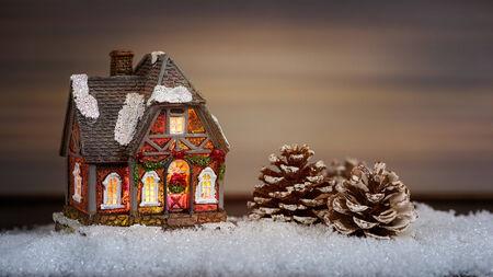 pomme de pin: Maison No�l et pomme de pin dans la neige, d�coration de no�l