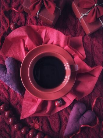 Cup of coffee, vintage hearts and gift boxes on a knitted sweater in red colors for Valentines Day