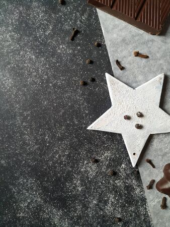 Chocolate, gingerbread and decorative white star with spices on a granite background