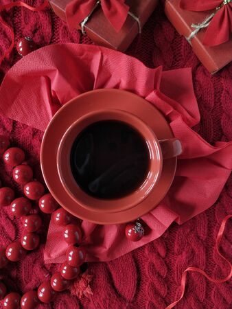 Cup of coffee and gift boxes on a knitted sweater in red colors for Valentine's Day Standard-Bild
