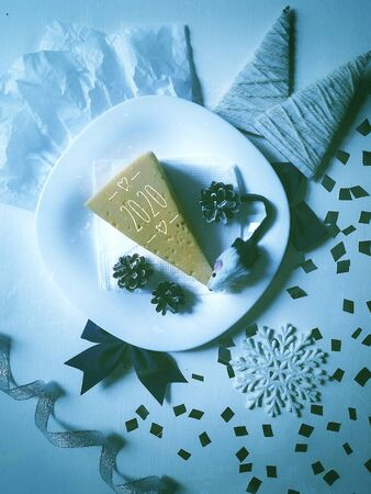 little mouse eats cheese from a white plate on New years Eve