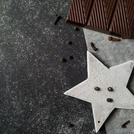 Chocolate and decorative white star with spices on a granite black and white background