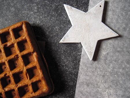 Belgian waffle and white wooden star on a granite glitter black and white background