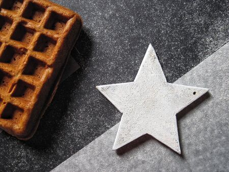Belgian delicious waffle and white wooden star on a granite black and white background
