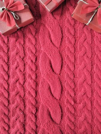 Gift boxes with a bows on a knitted wool sweater in rose colours for Valentine's Day Standard-Bild