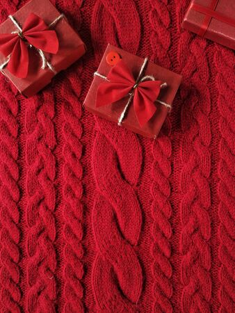 Gift boxes with a bows on a knitted wool sweater in red colours for Valentine's Day Standard-Bild