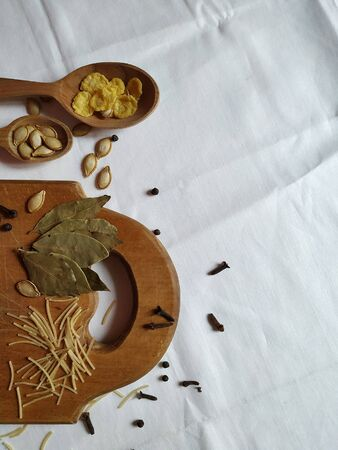 Kitchen wooden utensils with spices, herbs and seeds on a textile background Standard-Bild