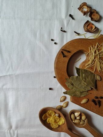 Kitchen wooden utensils with spices, herbs and seeds on a white textile background