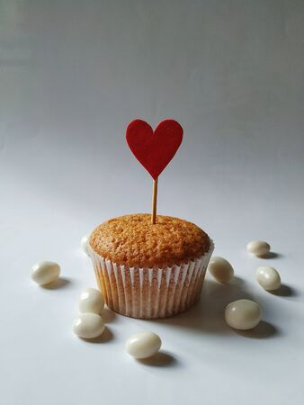 Sweet cupcake with a red  heart on a stick among chocolate nuts on a white background Standard-Bild