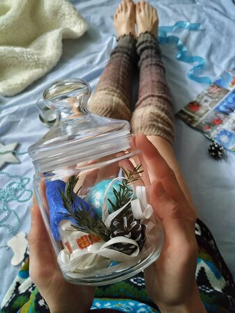 Young playful girl on a bed in warm knitted socks holds a glass jar with New Year, Christmas decorations