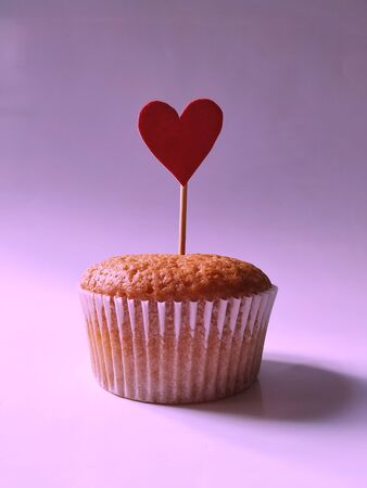 Sweet cupcake with a red heart on a stick on a pink background