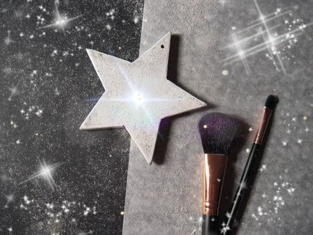 Makeup brushes and white shining star on a glitter black and white background