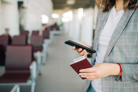 Young girl at the airport, standing in the waiting area before departure. Scrolling smartphone, holding passport and ticket. Closeup
