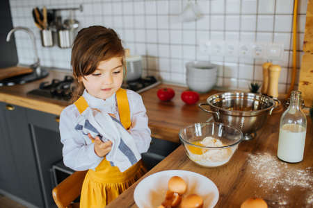 A little cute girl helping mother to bake cookies in the kitchen. Wiping hands with a towel near the bowl with flour.