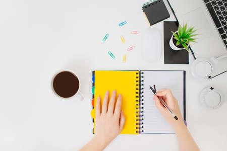 Posto di lavoro della donna, mani femminili che scrivono in un blocco note. Flatlay con mani, tazza da caffè, cuffie e blocco note. Archivio Fotografico