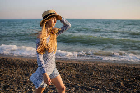 Beautiful young girl in a hat and light blue dress walking along the beach at sunset.