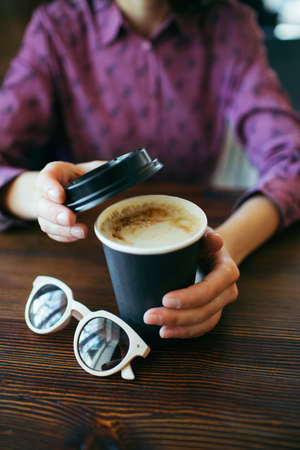 Female hands holding a cup of cappuccino with thick foam in black takeaway paper cup. Coffee take away. Stock Photo