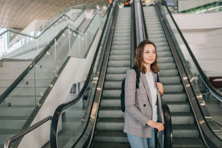 Young girl at the airport in grey casual clothes, standing with her suitcase and backpack near the escalator.