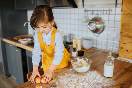 Little cute girl getting ready to bake a cake in kitchen.