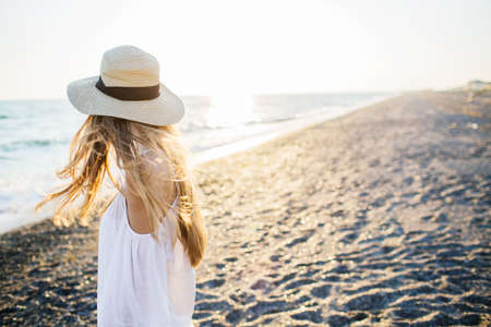 Young attractive long haired blonde girl in straw hat relaxing at the beach at sunset. Soft sunset light. 写真素材
