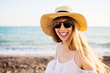 Young happy attractive girl in straw hat relaxing at the beach. Sunny weather and blue waves on the background.