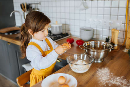 Little cute girl helping mother to bake a cake in the kitchen. Smashing eggs into a bowl with flour.