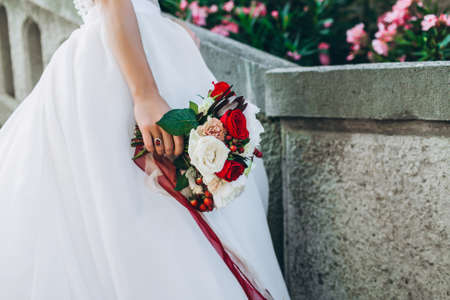 Wedding bouquet with bright flowers in brides hand. Close up, no face seen. Stock fotó