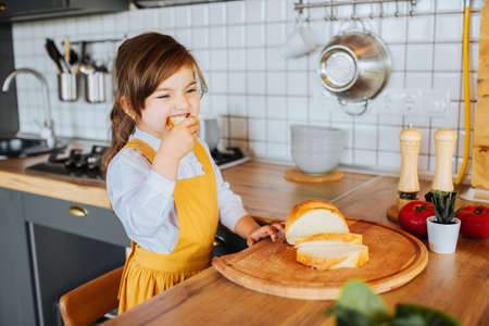 Cute little girl playing around in the kitchen, eating a loaf of bread at the table.