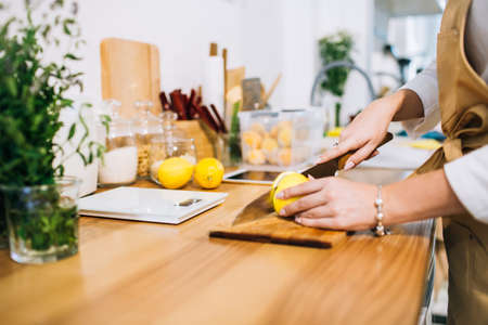 Female hands cutting lemon with a sharp knife in a bright minimalistic kitchen, getting ready for cooking.