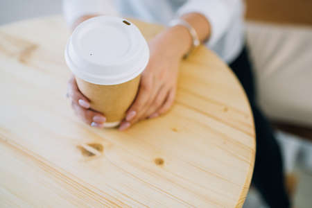 Female hands holding recyclable paper coffee cup at a cafe. Top view.
