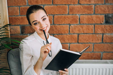 Happy young woman smiling, holding black notepad and a pen on a brick wall background.