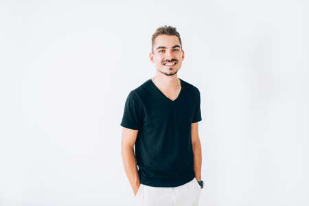 Happy young guy in black t-shirt posing on white isolated background. Standing with hands in the pockets, smiling.