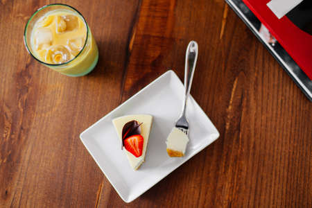 A piece of delicious cake with fresh strawberry on top. Cold coffee with ice beside, top view.