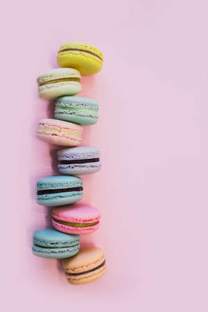 Macaron or macaroon biscuits on pastel pink background. Almond cookies of pastel colors. Top view. Copy space.