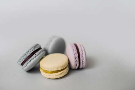 Closeup of sweet macaroon biscuits of pastel color lying in a pile on light grey background. Copy space.